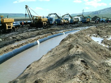 Oil pipeline floating due to flooding of the trench; 2nd pipe being welded
